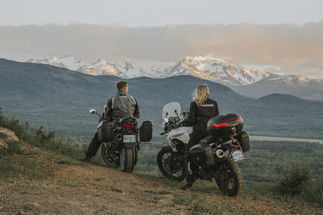 motorcyclists overlooking mountains